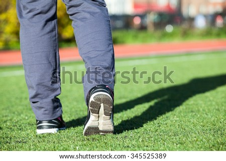 Sportsman legs in running shoes standing on the green grass