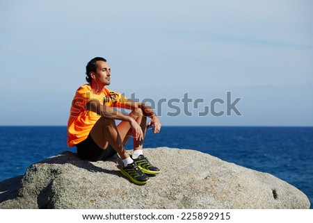 Sportsman listening to music on headphones outdoors, rest and relax after the training, male jogger seated on the beach enjoying music, fit man listening to music on mobile smart phone,sport lifestyle - stock photo