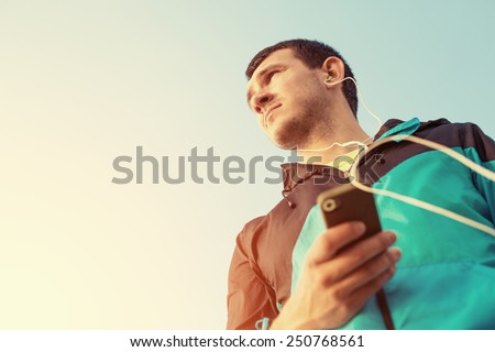 sportsman looking far away and listening music with phone in his hand - stock photo