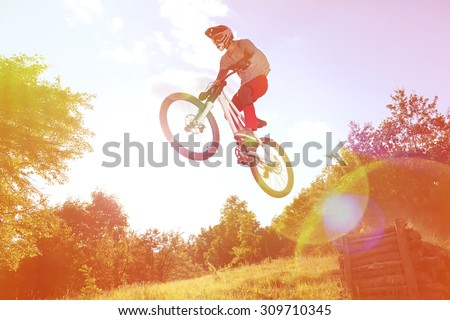 Sportsman on a mountain bike is flying in a jump from a springboard. Photo with special ligth lens effect - stock photo