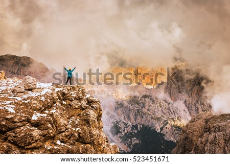 Sportsman on top of rock in Dolomite Alps