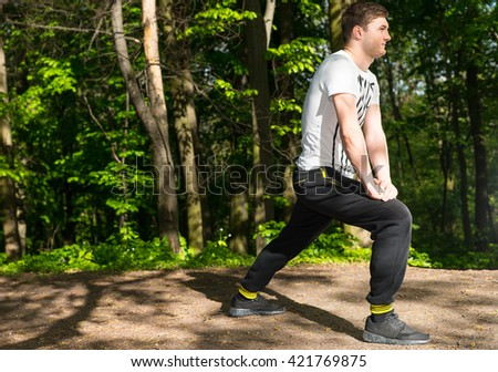 Sportsman Preparing For A Jog And Gets On One Knee In The Forest Alone - stock photo