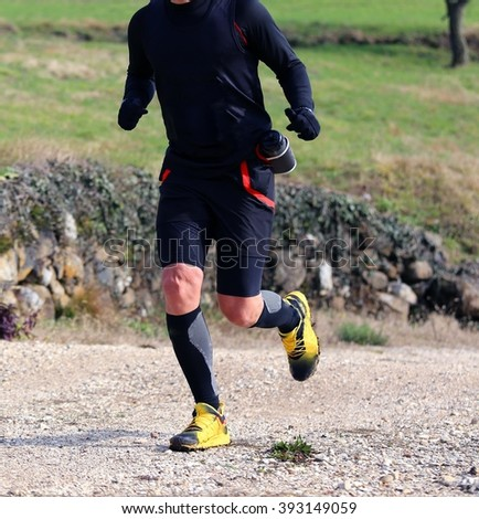 sportsman racer with running shoes runs during cross country on a country lane