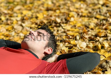 Sportsman resting and sleeping lying down on ground with autumn golden leaves. Man in relaxing, serene and peaceful attitude. - stock photo