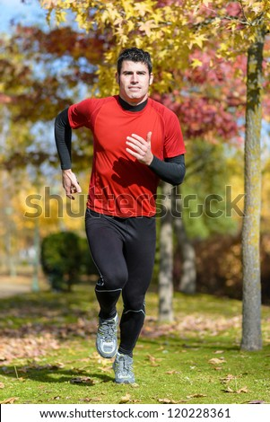 Sportsman running in park. Athletic male model training outdoors on autumn. - stock photo