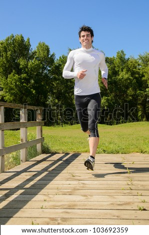 Sportsman running in park outside. Handsome young athlete running and working out on summer day. - stock photo