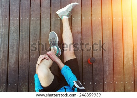 sportsman's legs sitting on the wooden floor with red sport plastic bottle, view from the top - stock photo