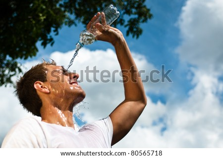 sportsman throwing water over his head for refreshment - stock photo