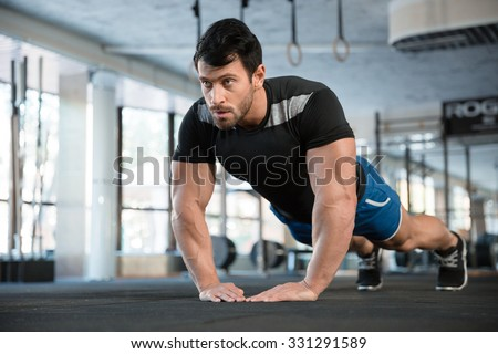 Sportsman wearing blue shorts and black t-shirt doing exercise for arms - stock photo