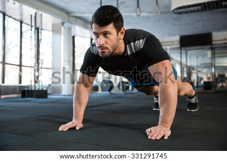 Sportsman wearing blue shorts and black t-shirt doing push-ups - stock photo
