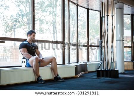 Sportsman wearing blue shorts and black t-shirt listening to music sitting on windowcill - stock photo