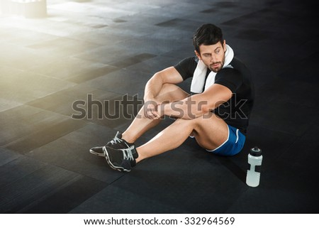 Sportsman wearing blue shorts and black t-shirt sitting on the floor in gym - stock photo