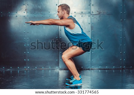 Sportsmen. fit male trainer man doing squats, concept fitness workout strenght power. - stock photo