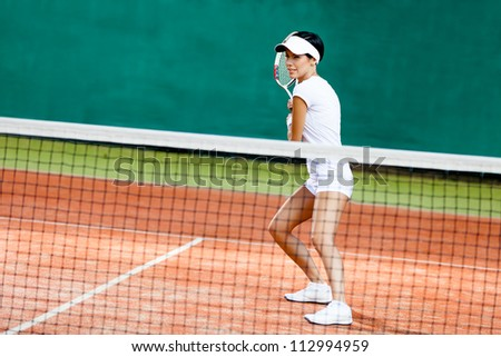 Sportswoman at the tennis court with racquet. Match - stock photo