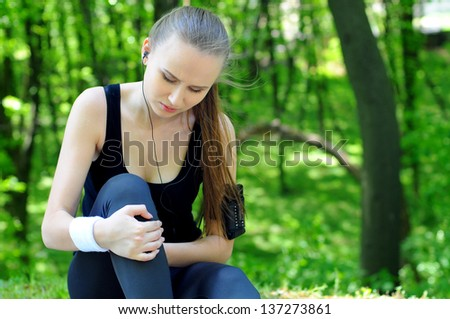 Sportswoman bended knee because of an ankle painful sprain injury. Female runner athlete lesion. - stock photo