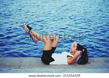 Sportswoman doing an active fitness training on concrete pier in beautiful day - stock photo