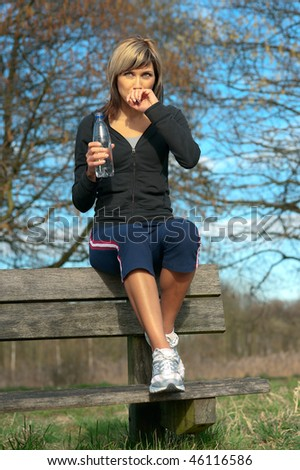 Sportswoman drinking water on a bench in a park. - stock photo
