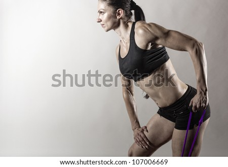 Sportswoman exercising with a resistance band on grey  background - stock photo