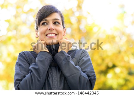 Sportswoman feeling cold on autumn sport training day. Female athlete getting ready before running or exercising outdoors. Caucasian sporty woman on fall copy space background. - stock photo