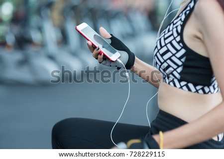 Sportswoman listening to music using phone app and smartwatch fitness activity tracker - heart rate monitor tracking her health progress on smartphone. Asian athlete in sportswear fashion clothing.