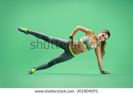 sportswoman performs the side rack with an emphasis on her left arm and leg, right hand on the waist, the right leg is raised to shoulder level; sportswoman on a green background in a gray sports suit - stock photo