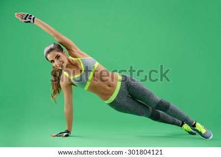 sportswoman performs the side rack with an emphasis on one hand and feet, the other hand raised above her head and straightened; sportswoman on a green background in a gray sports suit. - stock photo