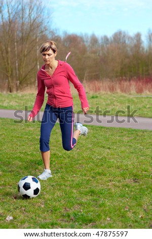 Sportswoman running outdoors after a ball  (playing football). - stock photo