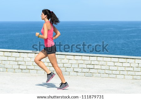 Sportswoman running outdoors on blue sea background. Caucasian brunette young model exercising on summer day. - stock photo