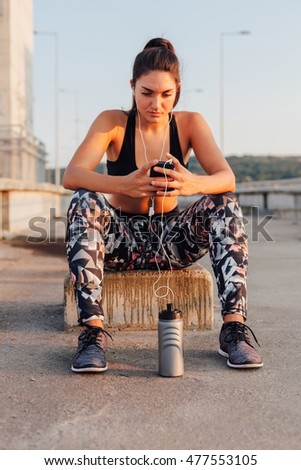 Sportswoman setting playlist on mobile phone for workout on the street
