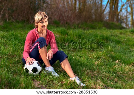 Sportswoman sitting on grass with a ball. - stock photo