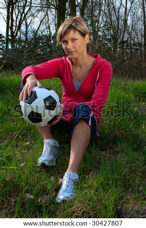 Sportswoman sitting on grass with a ball.