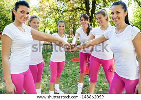 Sportswomen with hands together in huddle, agreement for fitness, - stock photo