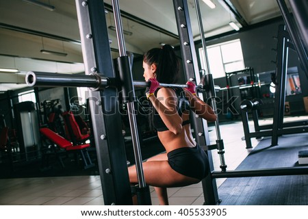 sportsy woman doing squats with a barbell in Smith machine