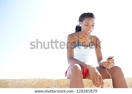 "Sporty ""african american"" woman sitting and getting ready for exercise, listening to music with her mp4 player against a bright blue sky. - stock photo"