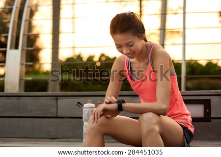 sporty asian chinese woman sitting outdoors checking workout time on wearable technology watch after run - stock photo