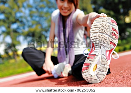 sporty asian girl doing stretching exercise - stock photo