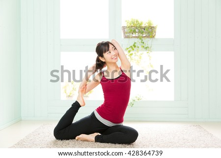sporty asian woman stretching in the room