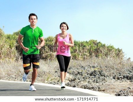 Sporty asian young couple running outside together on jogging track - stock photo