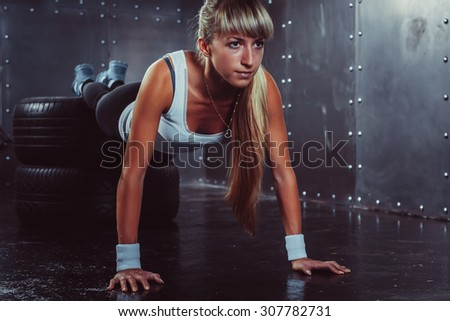 sporty athlete woman doing push ups on tire strength power training concept cross fit fitness workout sport and lifestyle. - stock photo