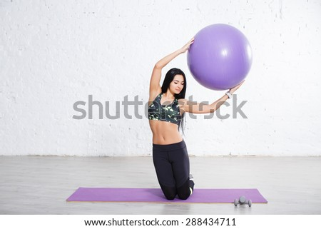 Sporty athletic brunette young woman doing exercise with violet fitball, kneeling on yoga mats. On white concrete wall background. - stock photo