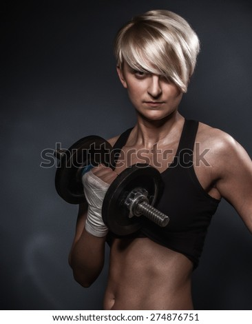 Sporty athletic woman ready for hard training with dumbbells on dark background