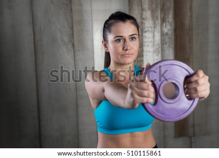 Sporty athletic woman ready for hard training with weights. Crossfit and fitness concept