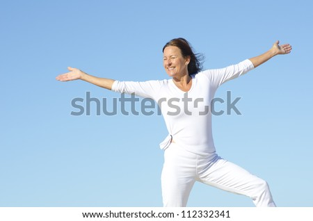 Sporty attractive senior woman being happy and active, isolated with blue sky as background and copy space - stock photo