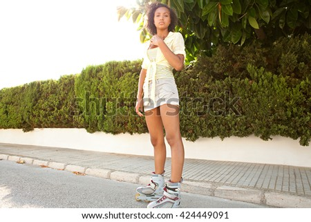 Sporty beautiful black teenager on roller blades, skating in a suburban street with the sun shining, outdoor activities. African american adolescent young woman, sport active lifestyle, home exterior.