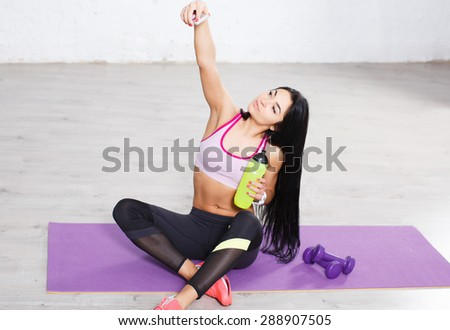 Sporty beautiful long hair brunette girl making selfie photo on smartphone during workout break.  - stock photo