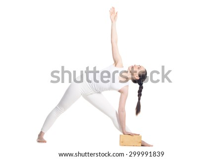 Sporty beautiful young beginning yoga female student standing in Utthita Trikonasana, Extended Triangle Pose with wooden block, studio full length profile view on white background, isolated - stock photo