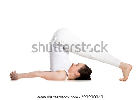 Sporty beautiful young woman doing halasana, plough pose (yin yoga snail posture), studio full length shot on white background, side view, isolated