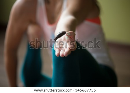 Sporty beautiful young woman in sportswear working out indoors, doing variation of Yoga Dandasana Posture, close-up, focus on fingers in Jnana mudra, horizontal image