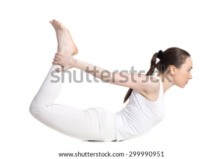 Sporty beautiful young woman in white sportswear doing backbend exercises, lying in dhanurasana, Bow Pose, studio full length side view, isolated - stock photo