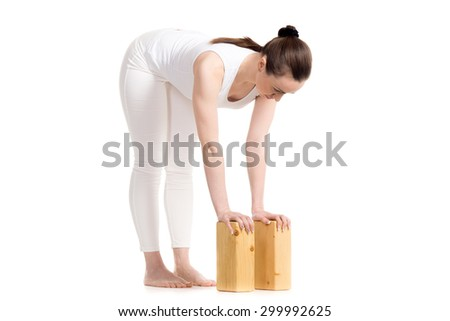 Sporty beautiful young woman in white sportswear doing variation of Ardha Uttanasana pose with wooden blocks, studio full length three-quarters view on white background, isolated - stock photo